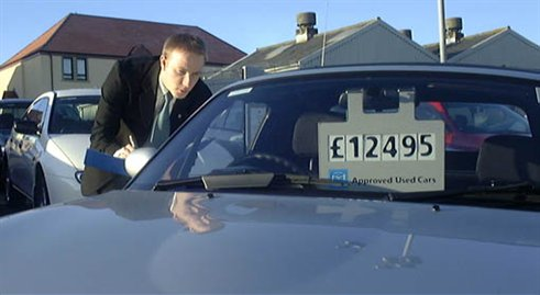 An Officer checks the mileage of a used car
